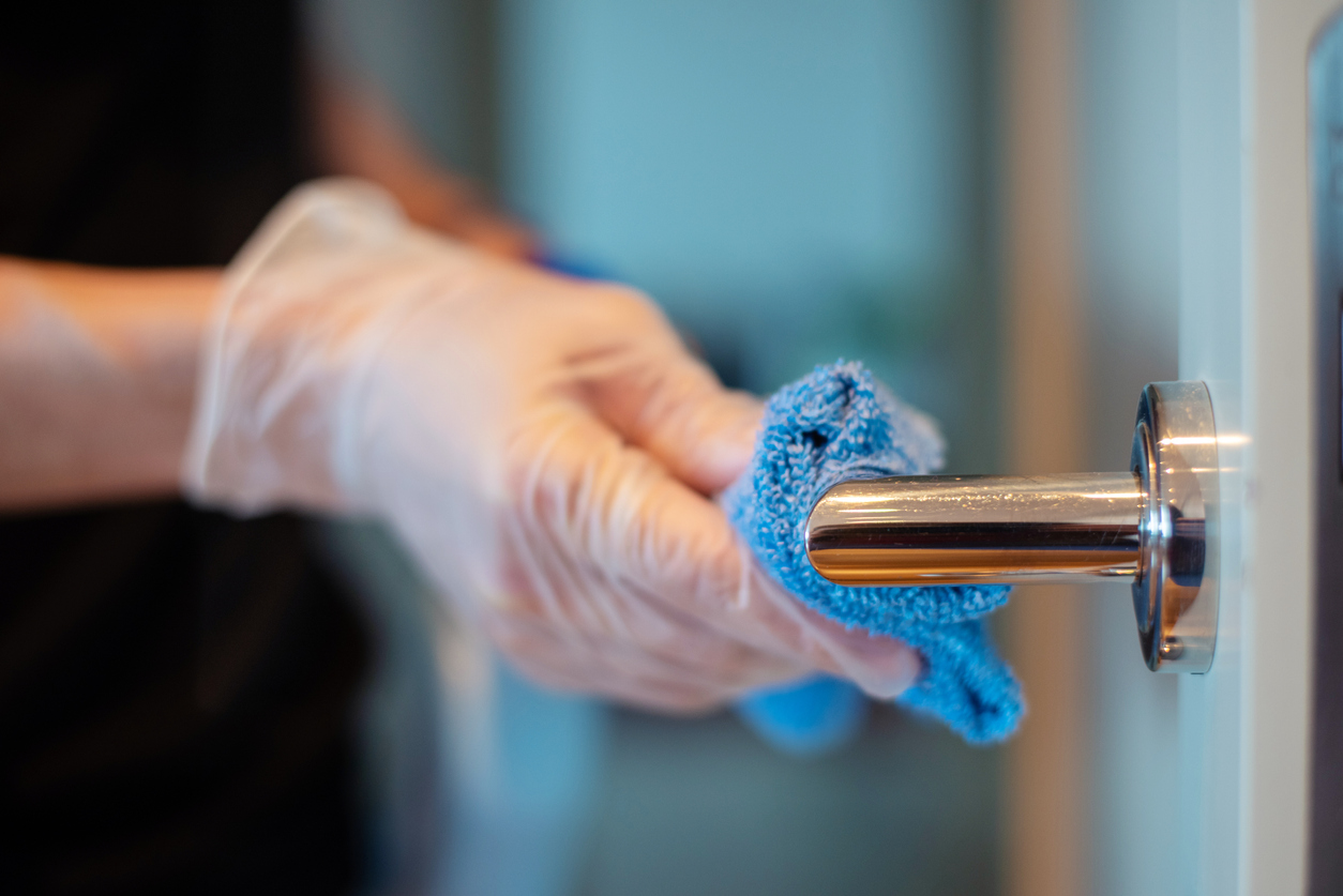 Closeup of the hands of a person disinfecting a door knob.