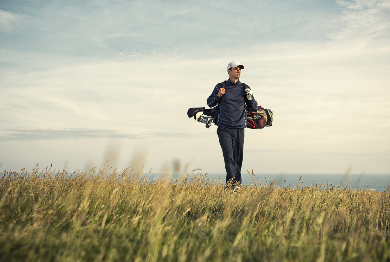 A male adult golfer walks to the green atop a links golf course in Woolacombe North DevonEngland.